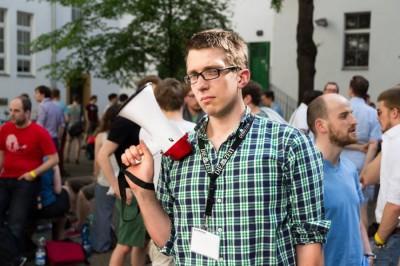 Public Speaking Champion Florian Umscheid mit finsterer Miene und der Siegertrophäe, dem Megaphon (c) Matthias Carcasona